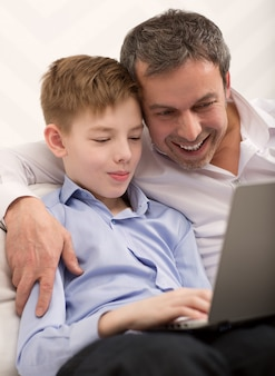 Happy dad and son with laptop at home