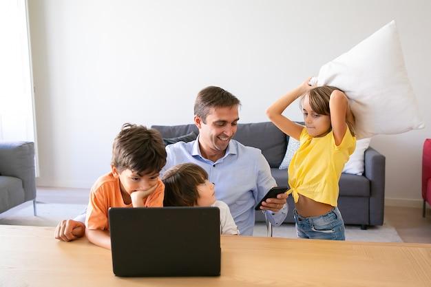 Papà felice utilizzando smartphone, seduto a tavola e bambini che giocano con lui. padre caucasico che lavora a casa, utilizza il laptop e guarda i bambini. concetto di paternità, infanzia e tecnologia digitale