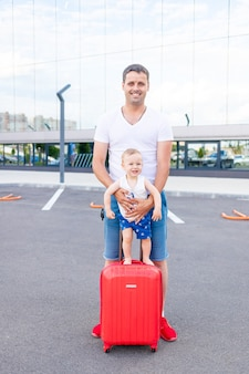 A happy dad with a baby son at the airport with a red suitcase goes on a trip or vacation