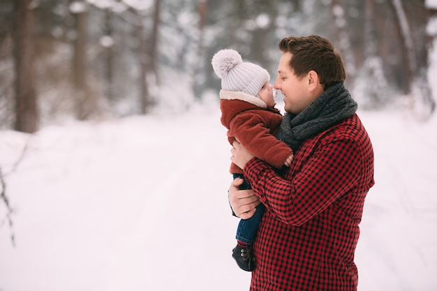 Happy dad with baby son while having fun in winter forest