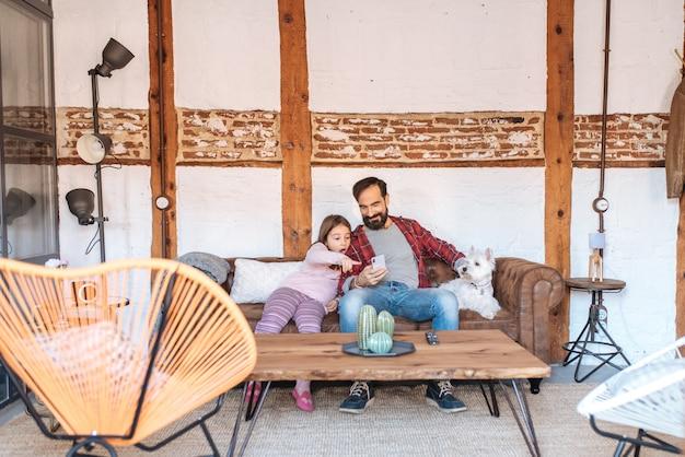 Счастливый папа со своей маленькой дочерью, глядя на телефон у себя дома, сидя на диване с собакой