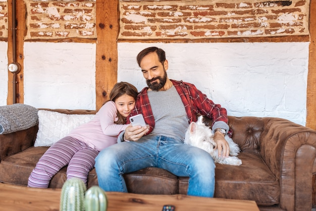 Happy dad with his little daughter looking on the phone at home sitting in the sofa with the dog