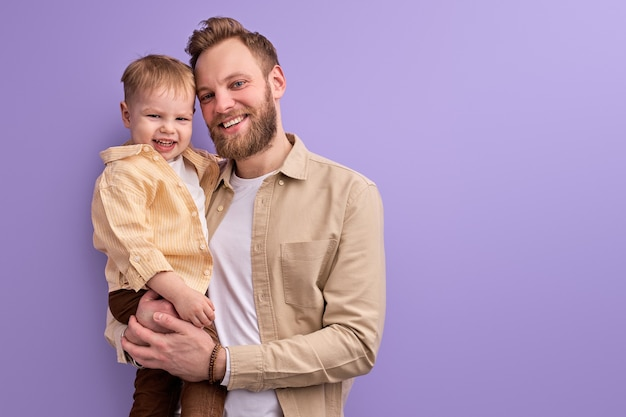 Happy daddy and little son posing at camera smiling isolated on purple wall