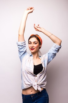 Felice adolescente danzante con le braccia in alto, su bianco. modella