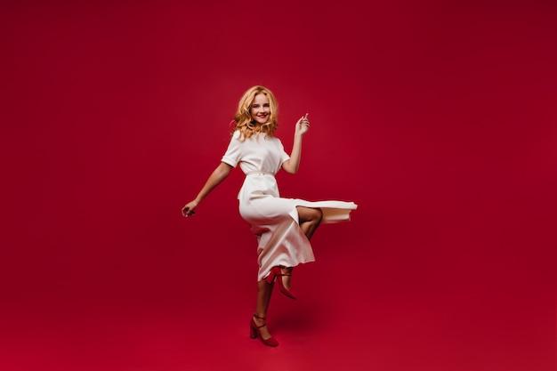 Счастливая танцевальная женщина улыбается на красной стене. очаровательная кудрявая девушка в длинном белом платье развлекается