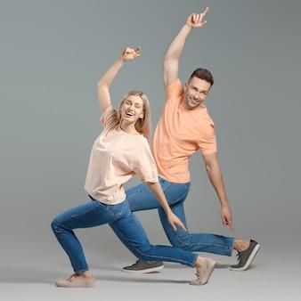 Счастливая танцующая молодая пара на серой поверхности