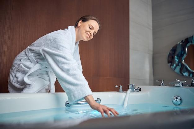 Счастливая темноволосая кавказская женщина в махровом халате, склонившись над ванной, наполненной водой
