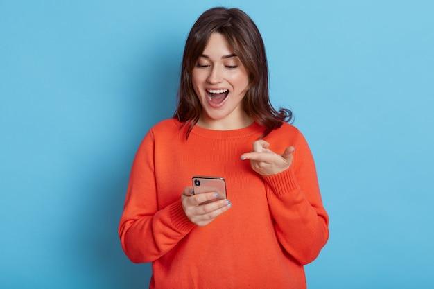 손에 스마트 폰으로 서서 열린 입과 파란색 벽 위에 고립 된 흥분된 표정으로 찾고 캐주얼 복장을 입고 행복 한 검은 머리 여성.