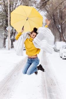 Счастливая темноволосая девушка, одетая в желтый свитер, джинсы и белый шарф, прыгает с желтым зонтиком на заснеженной улице в зимний день.