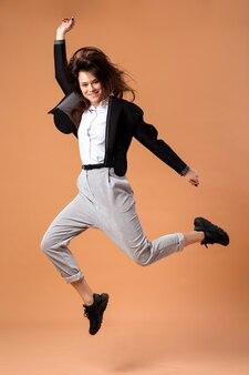 Счастливая темноволосая девушка в белой рубашке, серых брюках, черной куртке и черных кроссовках прыгает на бежевом фоне в студии.
