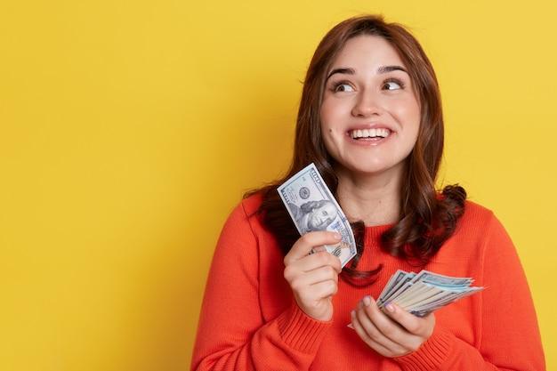 Счастливая темноволосая девушка в оранжевом свитере держит деньги в руках
