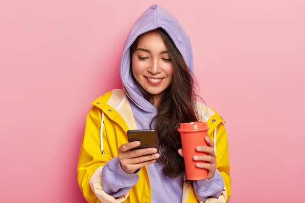 Happy dark haired girl wears hoody and raincoat, holds mobile phone, scrolls feed in socian networks, drinks coffee or tea