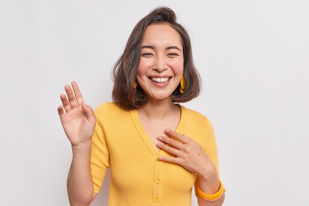 Happy dark haired pretty asian woman with positive expression laughs joyfully keeps hand raised smiles broadly wears yellow jumper earrings hears something funny isolated over white wall