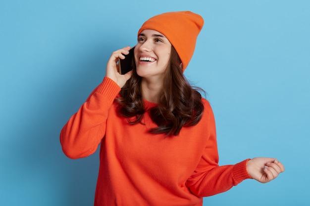 주황색 스웨터와 모자에 행복 한 검은 머리 여자는 파란색 벽 위에 고립 된 휴대 전화를 들고 긍정적 인 표정으로 멀리보고 스마트 폰을 통해 즐거운 대화를 나누었습니다.