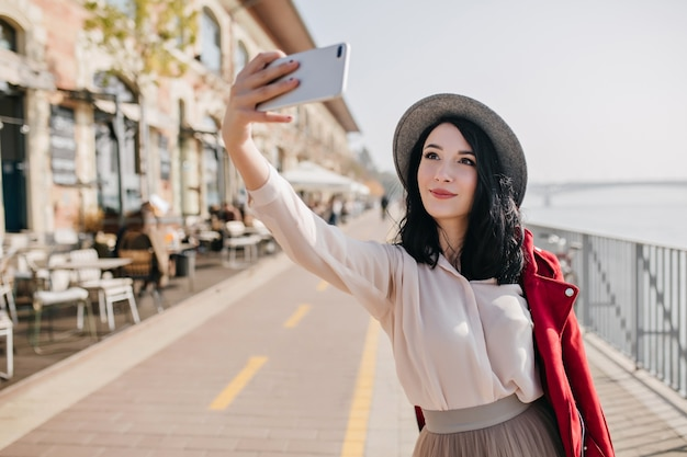 Happy dark-haired woman in romantic outfit making selfie near street cafe