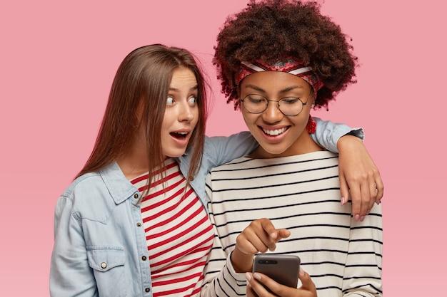 Felice donna afroamericana dalla pelle scura con taglio di capelli afro guarda felicemente smart phone, sorride volentieri, tiene smart phone