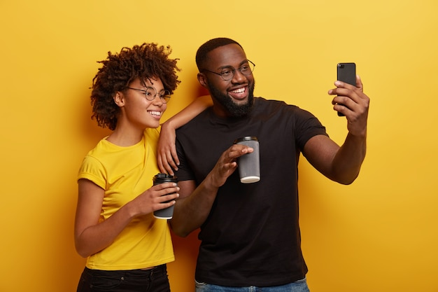 사랑에 빠진 행복한 어두운 피부 커플은 커피 휴식 시간 동안 재미 있고, 현대 휴대 전화에서 셀카 초상화를 만들고, 둥근 안경을 착용합니다.