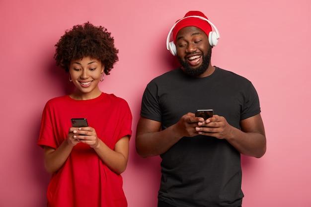 행복한 어두운 피부를 가진 커플은 서로 가까이 서 있고, 현대 기술과 장치에 중독되어 있고, 온라인 비디오 게임을하고, 행복한 기분을 가지고 있습니다.