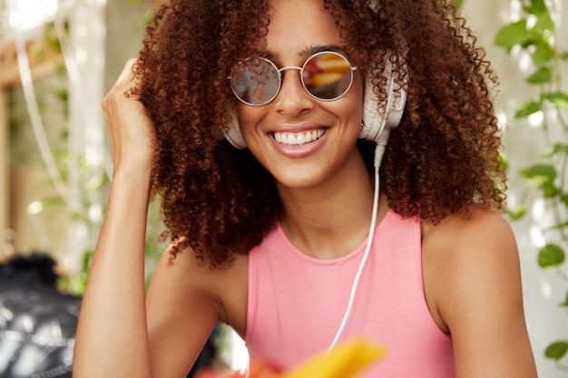 トレンディな色合いの幸せな暗い肌のカーリー女性モデル、大きなヘッドフォンで音楽を楽しむ、輝く笑顔を持っている、またはラジオを聴いている。美しいアフリカの女性はイヤホンでお気に入りの放送を聴きます