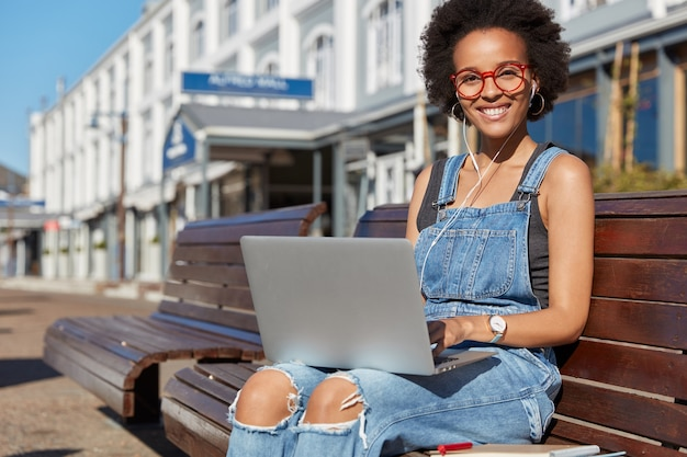 Happy dark skinned female designer watches tutorial about creative ideas, keeps portable laptop computer on knees, listens online news with earphones, wears spectacles and denim overalls poses outdoor