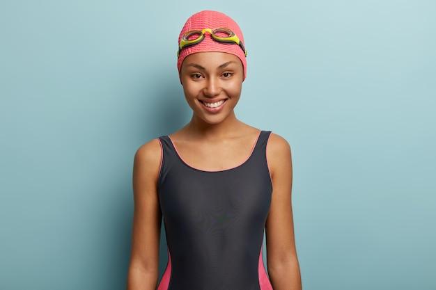 Felice femmina dalla pelle scura andando a nuotare, indossa cuffia rosa e occhiali protettivi