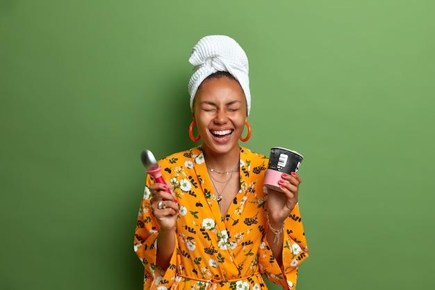 밝은 노란색 드레싱 가운을 입고 머리에 수건을 감싼 행복 어두운 피부 여성 모델은 녹색 벽에 고립 된 숟가락으로 맛있는 차가운 아이스크림을 먹는 것을 즐깁니다. 맛있는 음식.