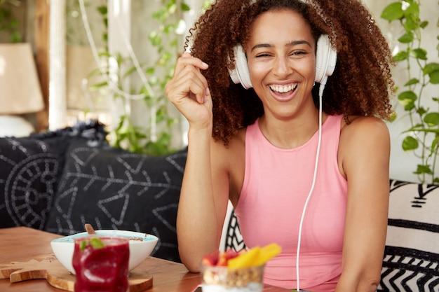 幸せな暗い肌の女性モデル、広い笑顔、ヘッドフォンでの逸話をオンラインで聞くと嬉しそうに笑い、現代のスマートフォンに接続し、ウェブサイトにインターネット投稿を公開し、カフェで休憩します。