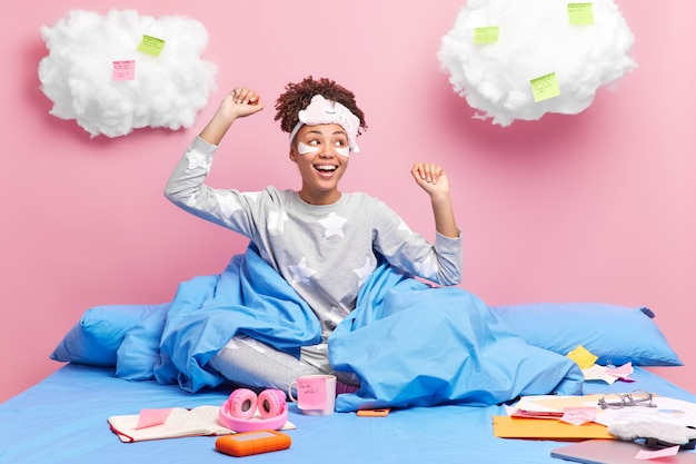 Felice studentessa dalla pelle scura in pigiama prepara il compito universitario a casa rimane nel letto comodo alza le braccia e balla