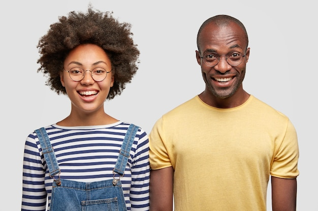 Happy dark skinned female with afro hairstyle, stands closely near african american guy, dressed in casual yellow t-shirt, isolated over white wall. people, ethnicity and friendship concept