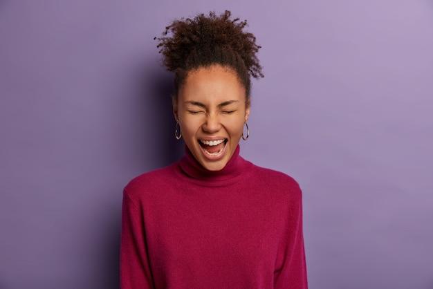 Счастливая темнокожая девушка не может сдержать смеха, прищуривается, хихикает над забавной шуткой, смотрит что-то очаровательное или забавное, носит бордовую водолазку, изолирована на фиолетовой стене, у нее позитивный день
