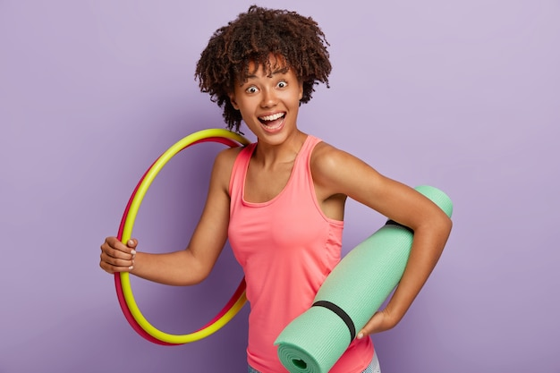 행복한 짙은 피부의 소녀는 청록색 매트, 두 개의 농구대를 들고 가정적인 분위기에서 운동하고 건강하고 건강하기 위해 스포츠를하고 보라색 벽에 실내에 서 있습니다. 스포츠 컨셉