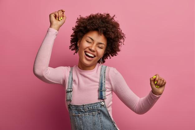 행복한 어두운 피부의 소녀는 삶의 모든 순간을 즐기고, 춤추고 움직이고, 팔을 들고 주먹을 쥐고, 눈을 감고, 기분이 좋고, 데님 사라 판과 터틀넥을 입고 분홍색 벽에 고립되어 있습니다.