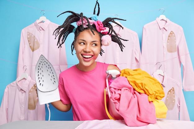 幸せな暗い肌の女の子はドレッドヘアを持っていますヘアカット塗られた口紅は夢のような表情で脇に集中しているアイロン台の近くで洗濯アイロンリネンポーズをします