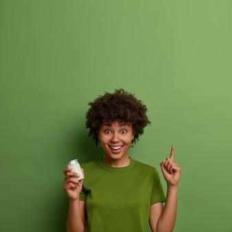 La ragazza felice dalla pelle scura conduce uno stile di vita sano, si tiene in forma, tiene in mano un barattolo di yogurt biologico a colazione, punta verso l'alto con il dito indice, mostra cibo o prodotto per una corretta alimentazione