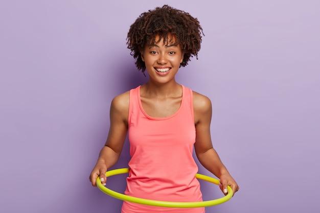 Felice ragazza dalla pelle scura ruota hula hoop, gode di esercizi attivi e allenamento ginnico, utilizza attrezzature per l'allenamento