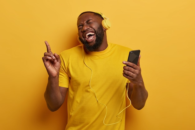 Happy dark skinned hipster guy with thick beard, laughs joyfully, points index finger above, holds modern cell phone, listens music in headphones