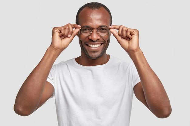 Felice insegnante dalla pelle scura indossa grandi occhiali rotondi, sorride positivamente