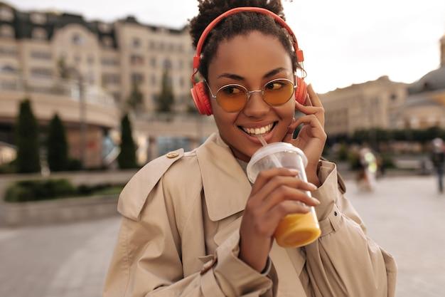 Happy dark-skinned woman in beige trench coat and eyeglasses drinks orange juice, listens to music in headphones and smiles outside