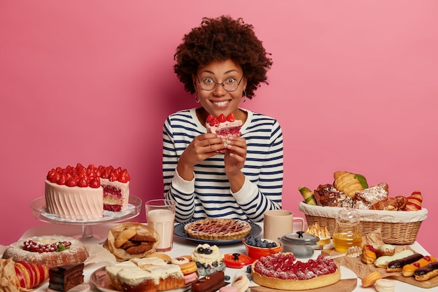 Happy dark skinned woman eat tasty strawberry cake, wears striped jumper, poses at table overload with desserts, gets great pleasure, poses over rosy wall