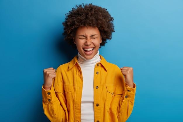 幸せな暗い肌の女性は成功の瞬間を楽しんで、勝利または素晴らしい結果を祝い、喜びを感じ、重要な目標または達成を獲得します