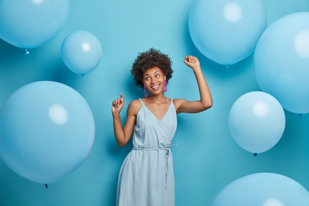 Happy dark skinned woman enjoys music at party, dances carefree, has fun and moves with rhythm of merry song, dressed in festive outfit, isolated over blue wall with decorated air balloons.