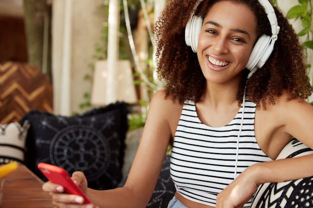 Happy dark skinned woman listens favourite song in headphones, chats online on smart phone, wears casual striped t shirt, downloads popular tracks in playlist. african female entertains at cafe