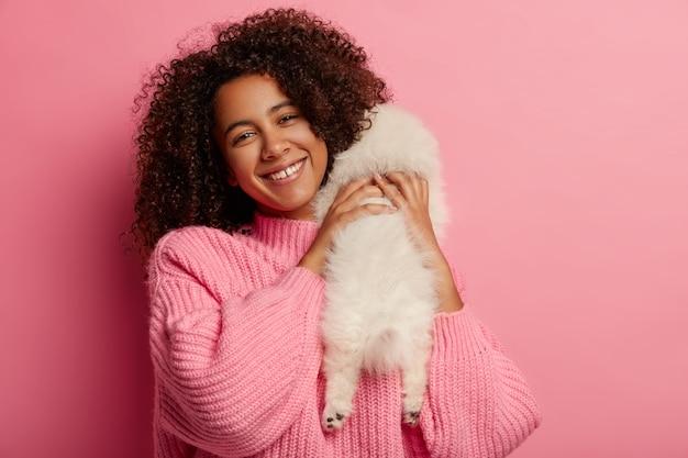 幸せな暗い肌の女性は白いスピッツ犬と遊ぶ