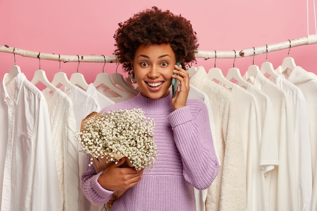 Happy dark skinned woman stands near home closet with white plain clothes on hangers, calls friend, shares emotions after first date, holds bouquet.