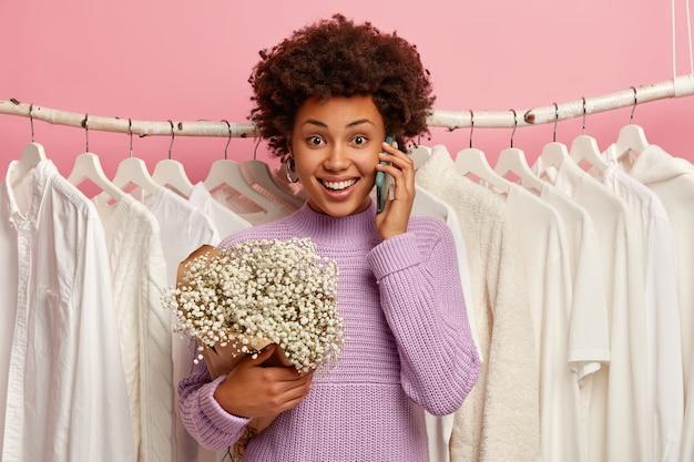 Felice donna dalla pelle scura si trova vicino all'armadio di casa con vestiti semplici bianchi sui ganci, chiama un amico, condivide le emozioni dopo il primo appuntamento, tiene il bouquet.