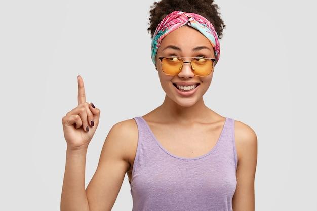 幸せな暗い肌の女性は流行の色合いを着ています