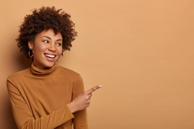 Felice donna dalla pelle scura con i capelli afro da parte con il dito indice in una pubblicità o in un grafico, racconta notizie estremamente buone, suggerisce il miglior affare di sempre, vede il prodotto preferito in negozio, indossa un dolcevita