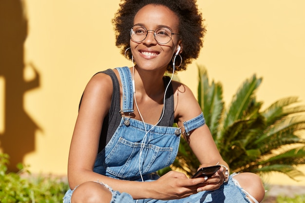 Happy dark skinned woman with afro haircut, uses app on mobile phone for listening music, enjoys good sound, wears jean dungarees, sits crossed legs, models over yellow wall with tropical plants