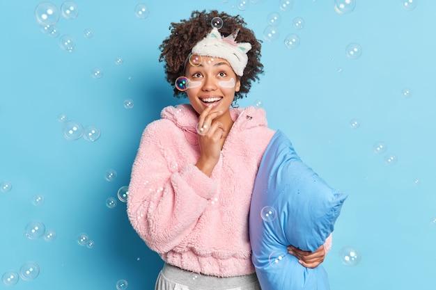 好奇心旺盛な表情で上に集中した巻き毛の幸せな黒髪女性が優しく微笑む