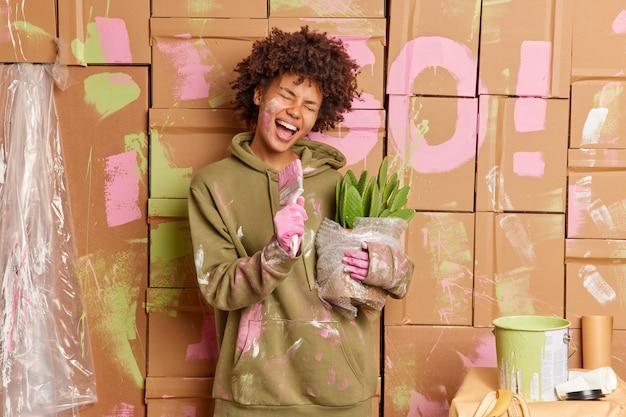 Felice giovane donna dalla pelle scura fa riparazioni in appartamento si diverte dopo aver dipinto i muri canta a pennello r